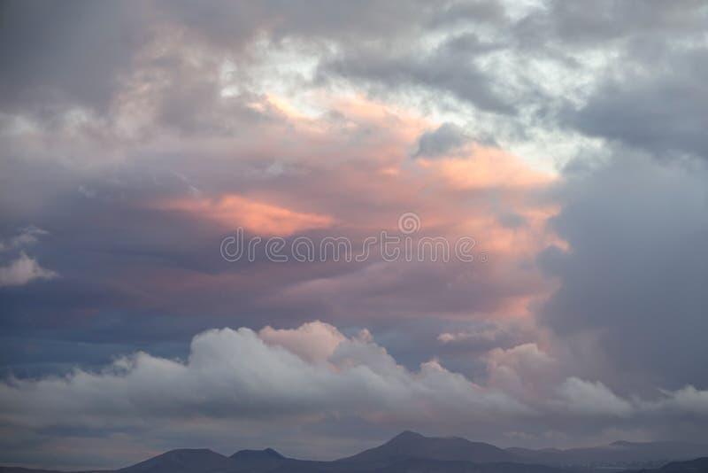 Nuages colorés sur la gamme de montagne au coucher du soleil photographie stock