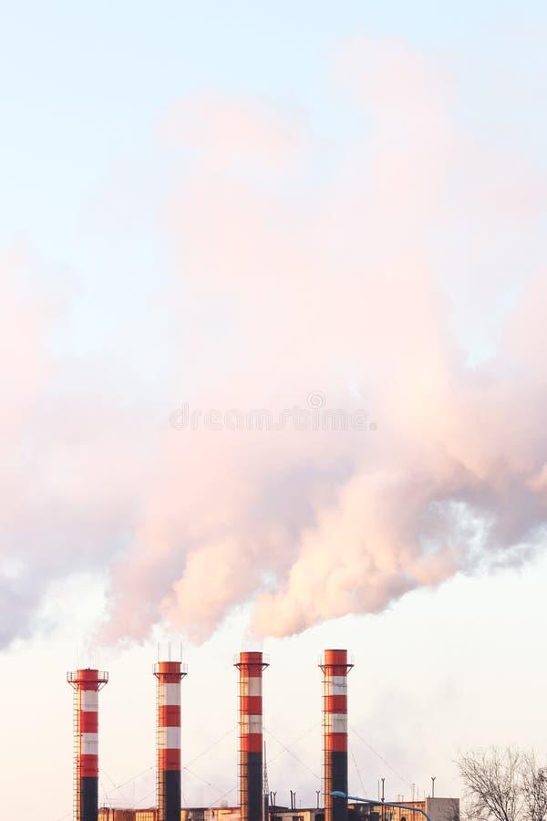 Nuages de fumée des quatre cheminées industrielles contre le ciel Pollution atmosphérique, problèmes environnementaux photos libres de droits