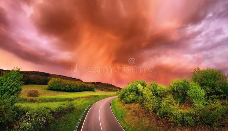 Nuages de pluie fascinants au-dessus d'une route au coucher du soleil photo libre de droits