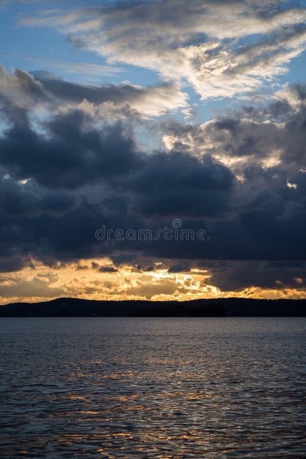 Nuages dramatiques au-dessus d'un lac au coucher du soleil photographie stock