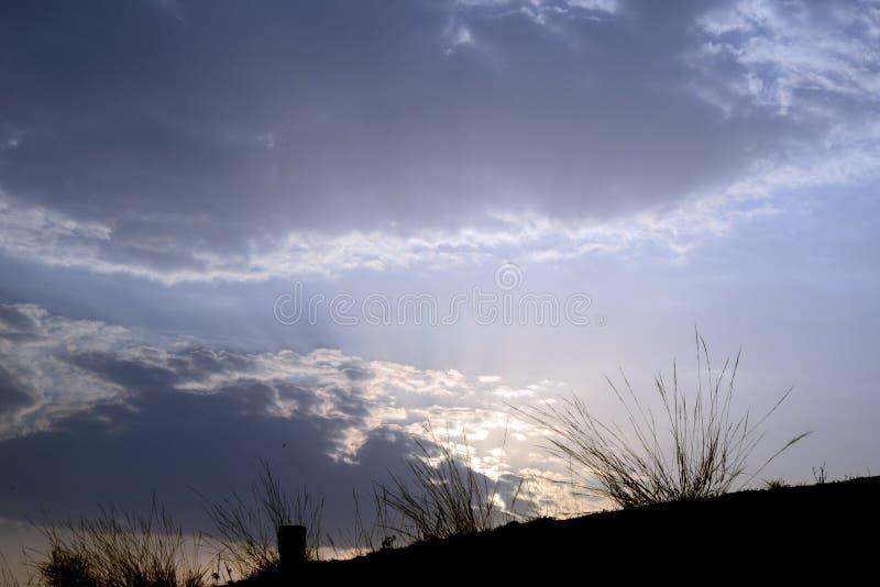 Nuages et ciel avec des buissons sur la colline photographie stock