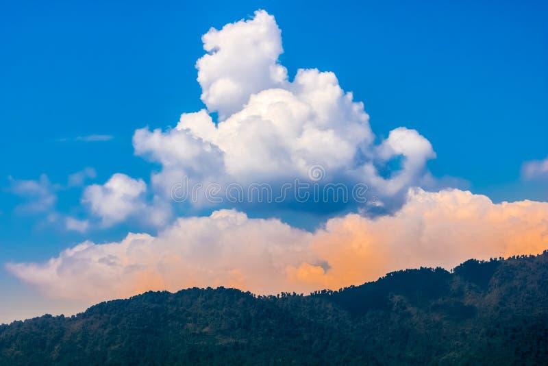 Nuages et ciel colorés derrière la montagne image stock