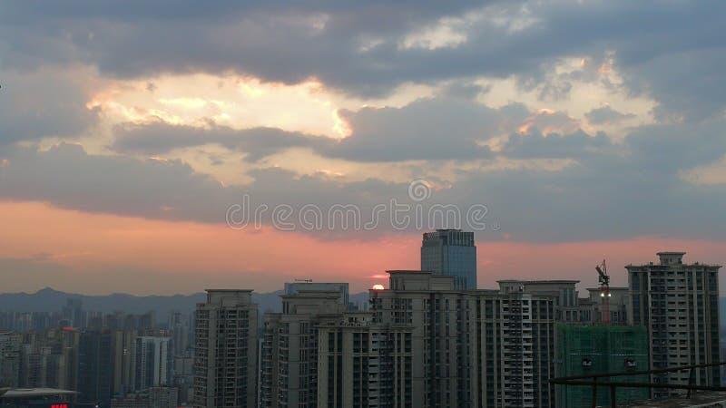 Nuages et ciel dramatiques au-dessus de ville au coucher du soleil photos stock