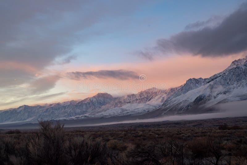 Nuages et ciel roses de lever de soleil au-dessus de gamme de montagne neigeuse image libre de droits