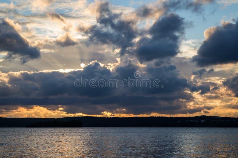 Nuages foncés et dramatiques, rayons de soleil et un lac images libres de droits
