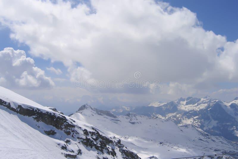 Nuages moulant des ombres sur la gamme de montagne neigeuse photos stock