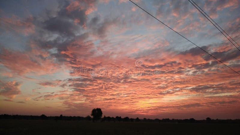 Nuages oranges et rouges ardents au coucher du soleil image stock