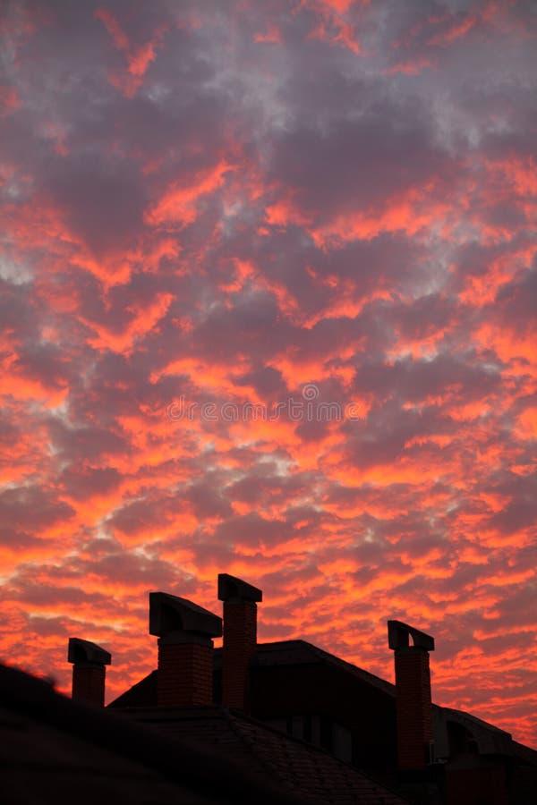 Nuages oranges vibrants au-dessus des cheminées de dessus de toit photo stock