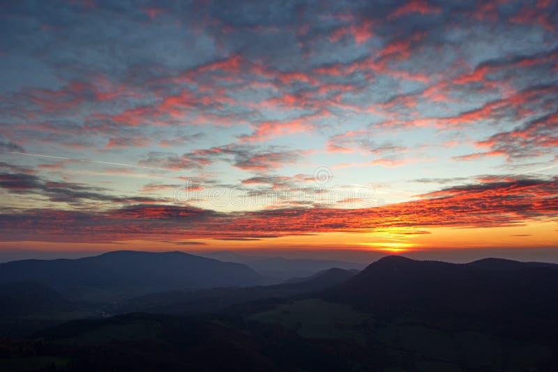 Nuages peu communs au-dessus des montagnes dans le temps de coucher du soleil image stock