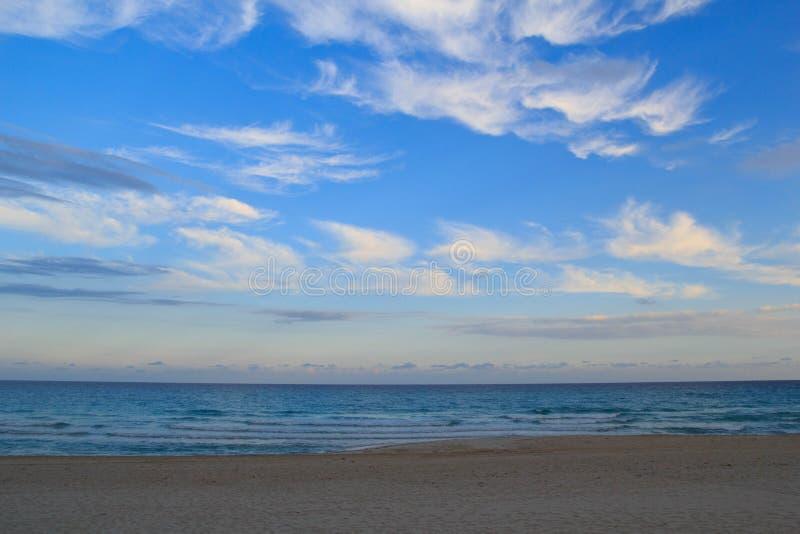 Nuages plumeux pendant le matin à la plage images stock