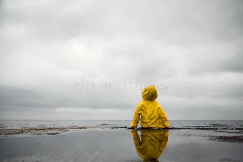 Nuages pluvieux Enfant dans un imperméable jaune photographie stock
