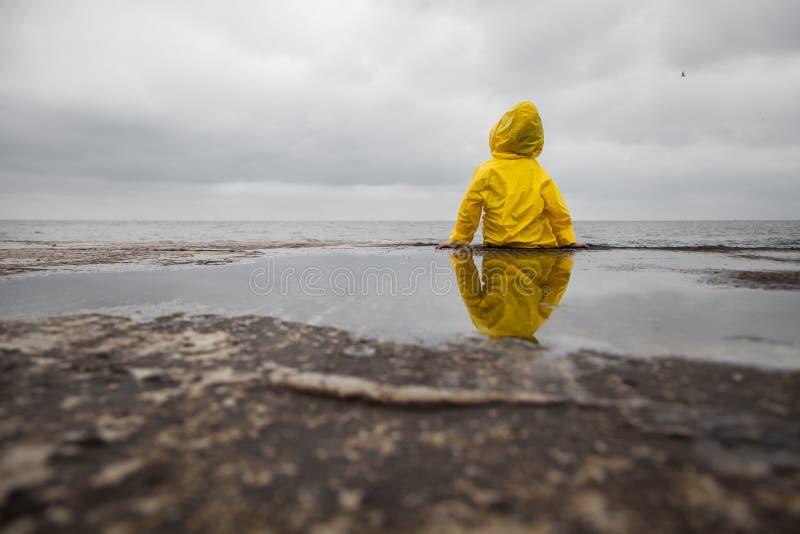 Nuages pluvieux Enfant dans un imperméable jaune photo libre de droits
