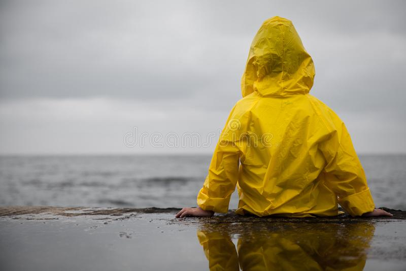 Nuages pluvieux Enfant dans un imperméable jaune image libre de droits