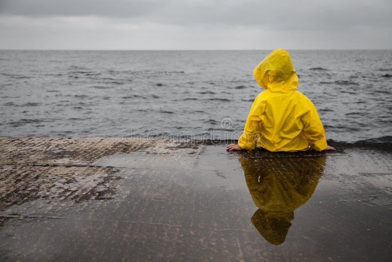 Nuages pluvieux Enfant dans un imperméable jaune photo stock