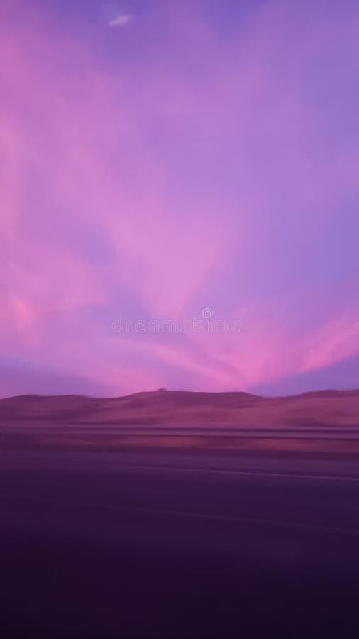 Nuages pourpres et roses pendant le coucher du soleil photos stock