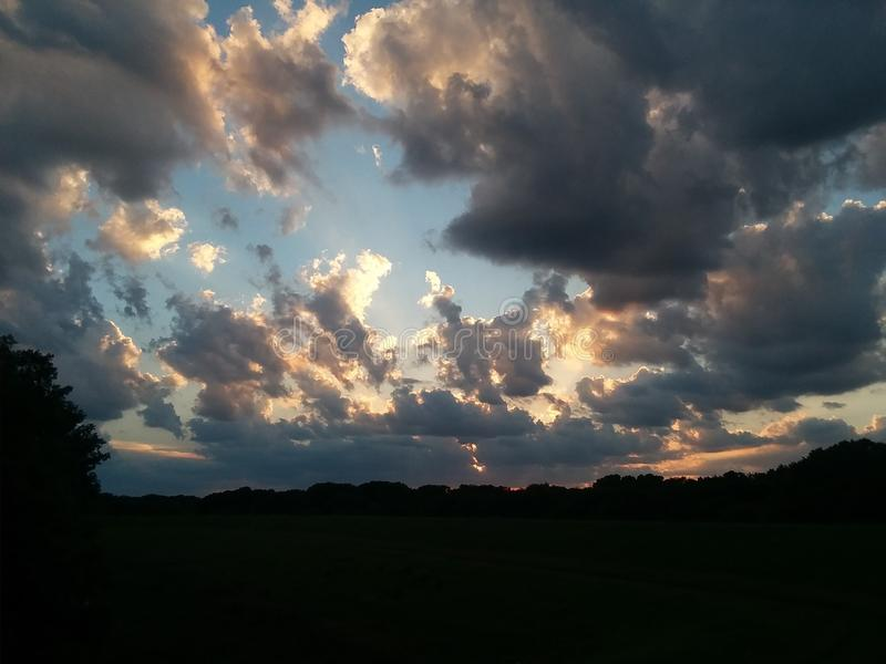 Nuages rétroéclairés du coucher du soleil Soir été photographie stock libre de droits