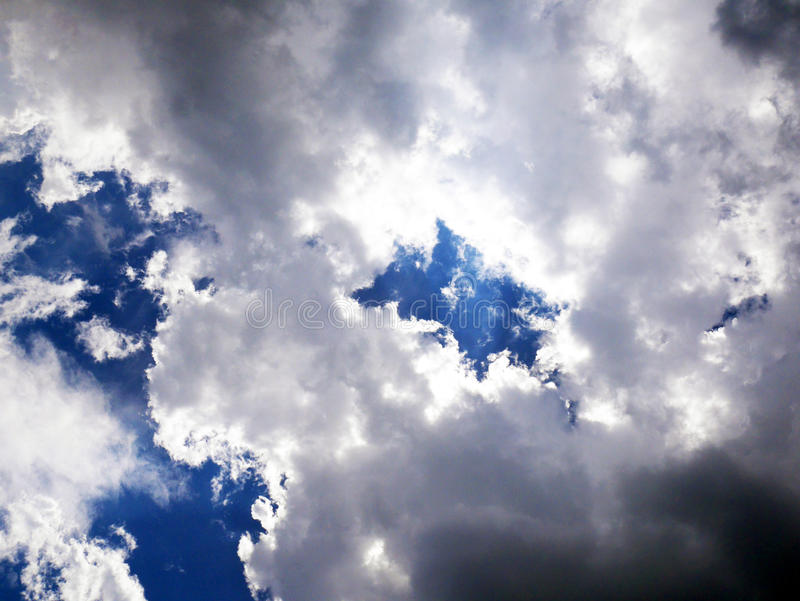 Nuages rétro-éclairés sur le ciel bleu photographie stock libre de droits