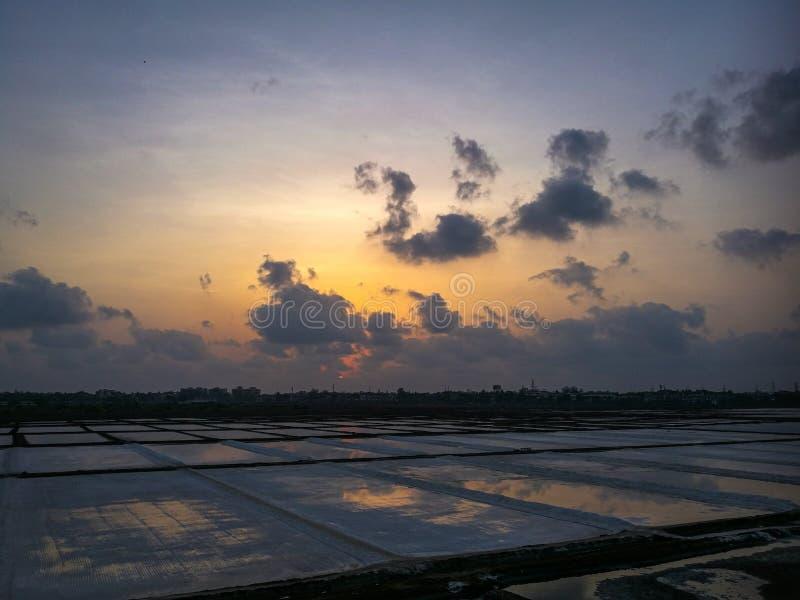 Nuages romantiques recueillant à la soirée colorée près du marais salant photographie stock libre de droits