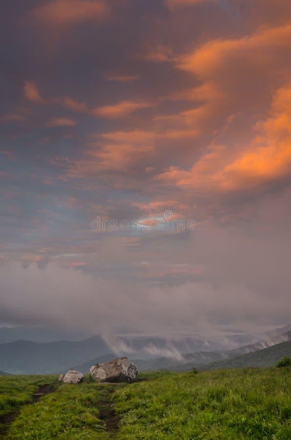 Nuages roses au-dessus des roches sur chauve rond photos stock