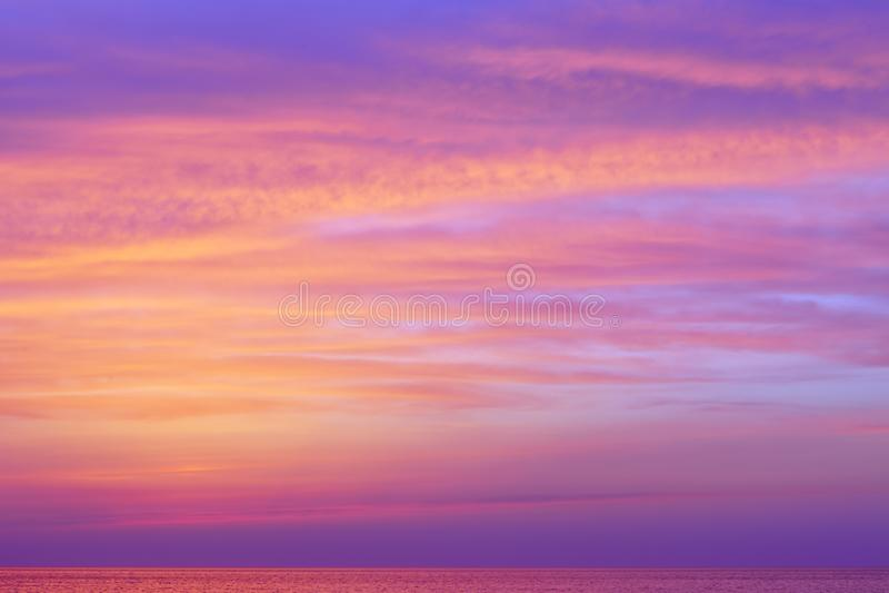 Nuages roses fantastiques au-dessus de la mer après coucher du soleil photo libre de droits