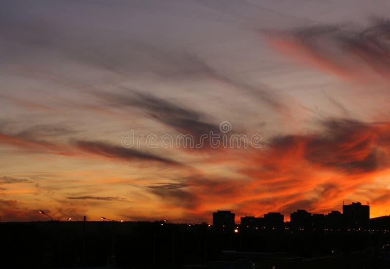 Nuages rouges au-dessus de ville images stock
