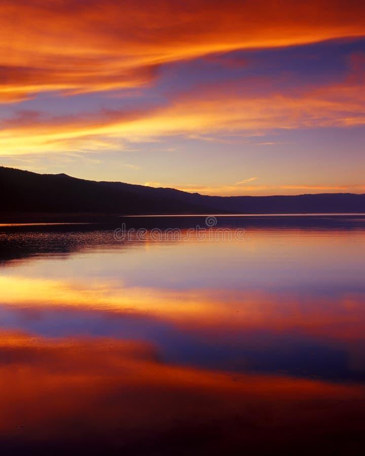 Nuages Wispy au-dessus de lac au coucher du soleil images stock