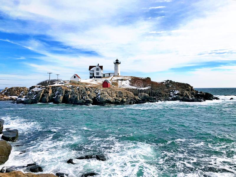 Nubble lighthouse winter view after snow. The Cape Neddick Light is a lighthouse in Cape Neddick, York, Maine,United States.It stands on Nubble Island off Cape stock photography