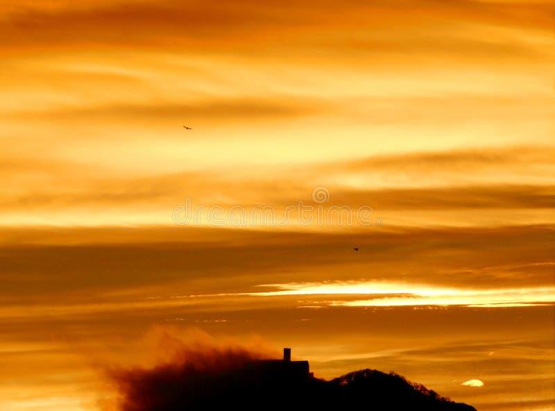 Nube behing ocultada castillo durante salida del sol imágenes de archivo libres de regalías