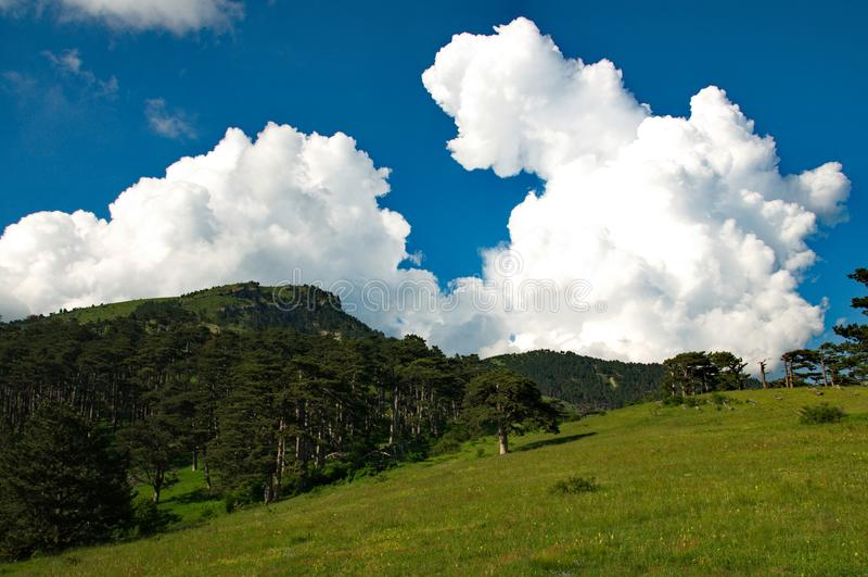 Nube blanca en el cielo azul sobre las montañas imagenes de archivo