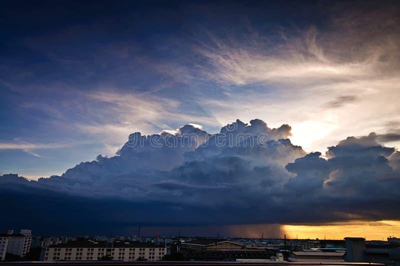 Nube di nimbus del cumulo e piovere sopra la città fotografia stock