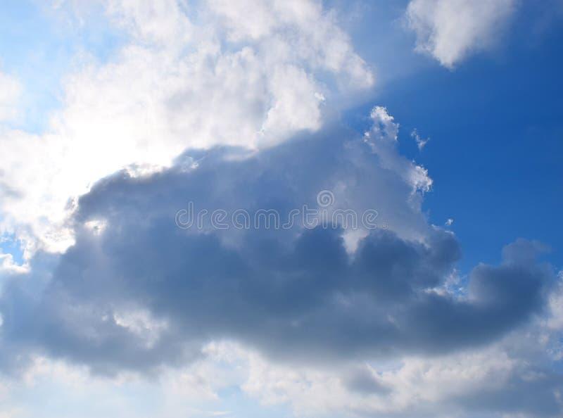 Nube oscura en el cielo azul con Sun ocultado detrás de las nubes - fondo natural abstracto imagen de archivo