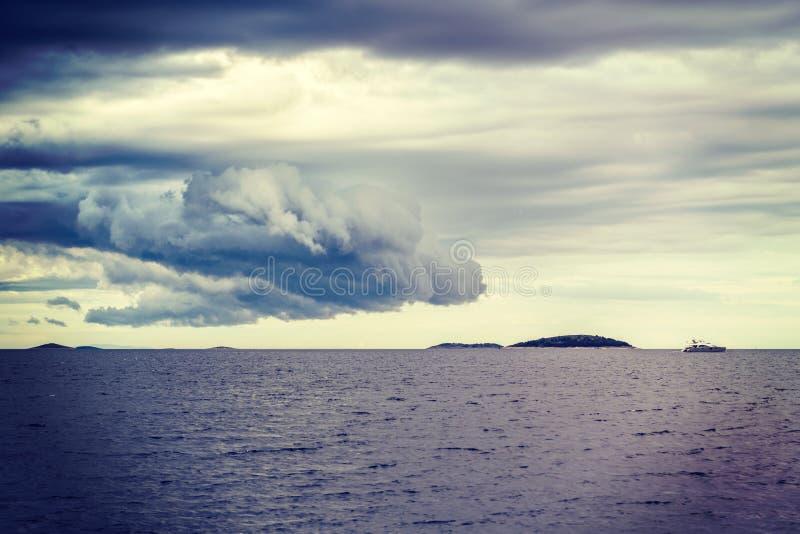 Nube pesada, isla abandonada y yate foto de archivo libre de regalías
