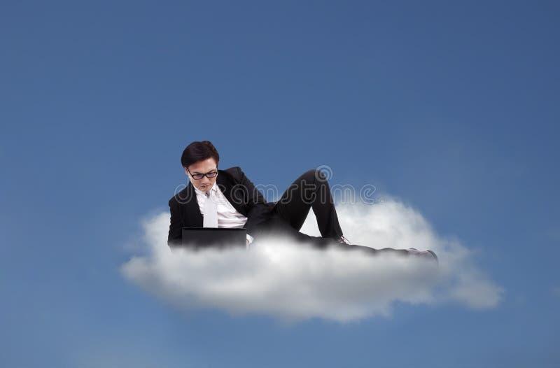 Nube que computa: Funcionamiento asiático del hombre de negocios foto de archivo