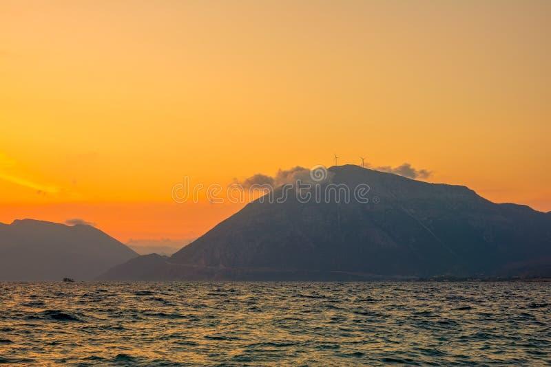 Nube y granjas eólicas en lo alto de una costa montañosa al atardecer foto de archivo libre de regalías