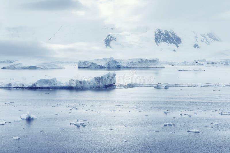 Nubes bajas sobre las montañas y los pedazos de la flotación del hielo del centro de investigación de Lockroy del puerto imágenes de archivo libres de regalías