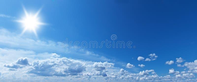 Nubes blancas del montón y sol brillante en el cielo azul imagen de archivo