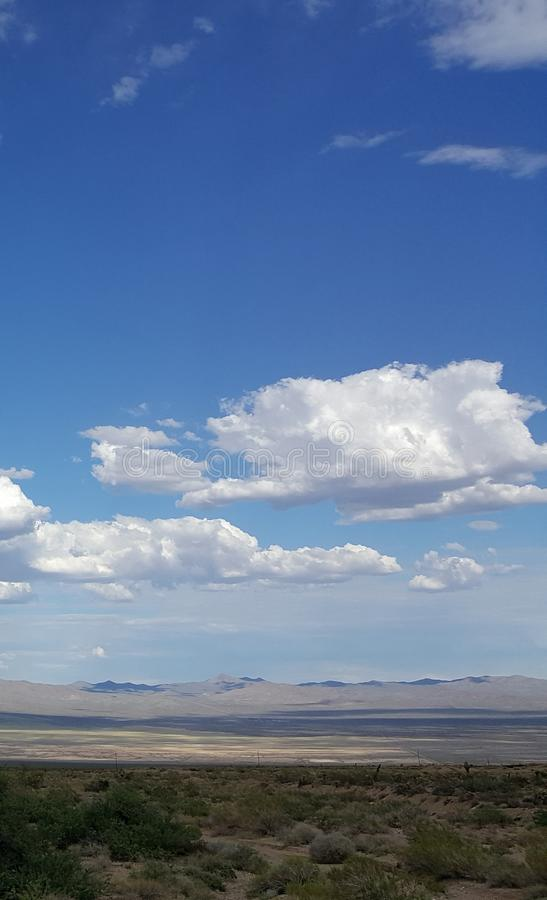 Nubes blancas en cielo azul sobre paisaje de la montaña del desierto foto de archivo
