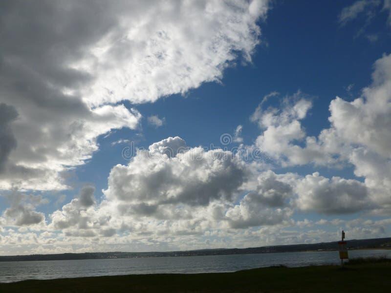 Nubes brillantes contra el azul imagenes de archivo