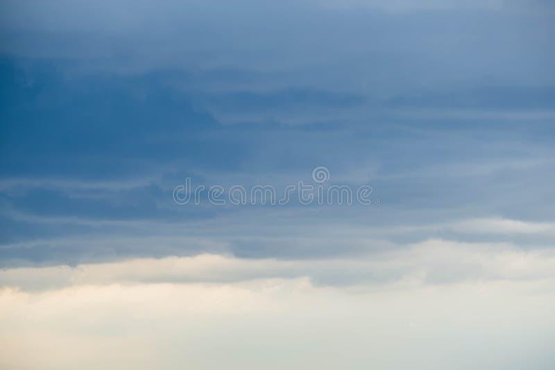 Nubes cerca de la puesta del sol antes del cielo azul de la lluvia foto de archivo