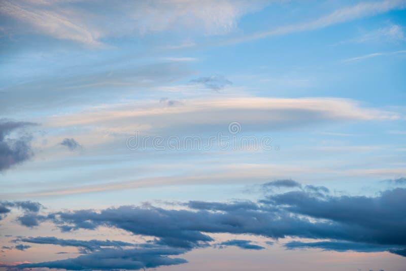 Nubes cerca de la puesta del sol antes del cielo azul de la lluvia imagenes de archivo