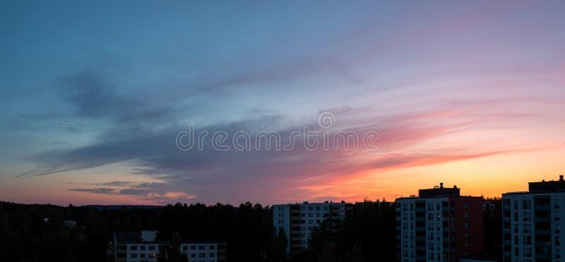 Nubes coloridas de la puesta del sol en la oscuridad sobre edificios de la ciudad foto de archivo libre de regalías