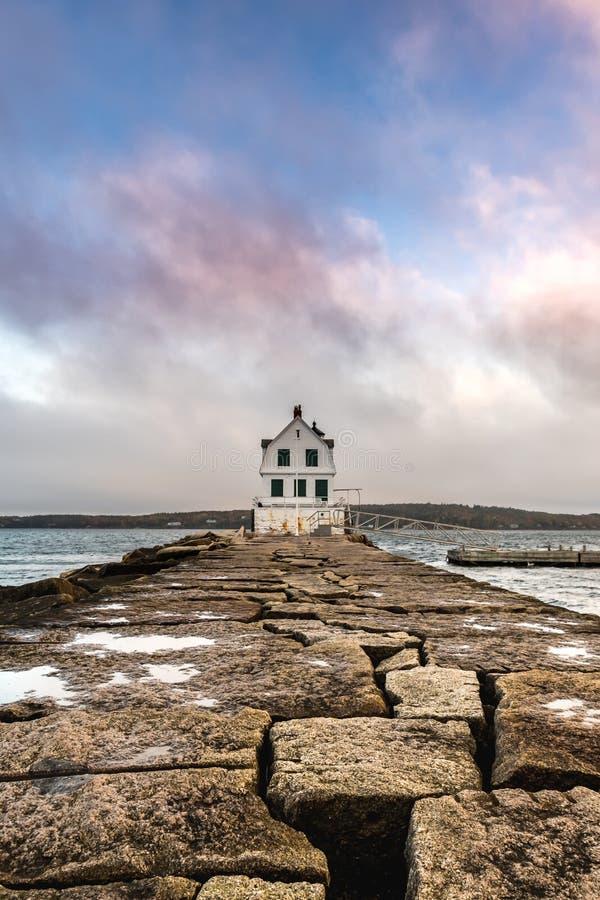 Nubes coloridas sobre la luz del rompeolas del puerto de Rockland imagenes de archivo