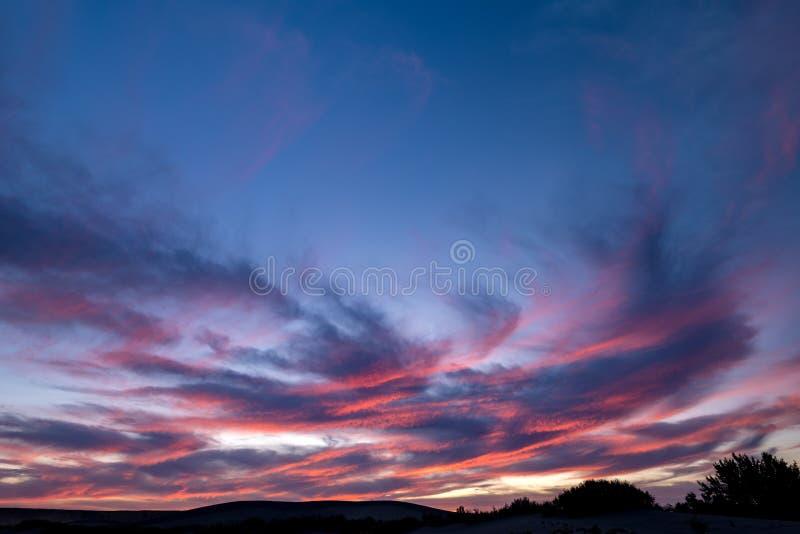 Nubes coloridas Wispy de la puesta del sol sobre las colinas de la arena en el desierto imagenes de archivo