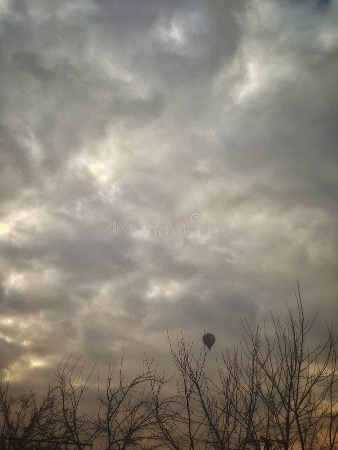 Nubes de árboles secados y de un globo imagen de archivo