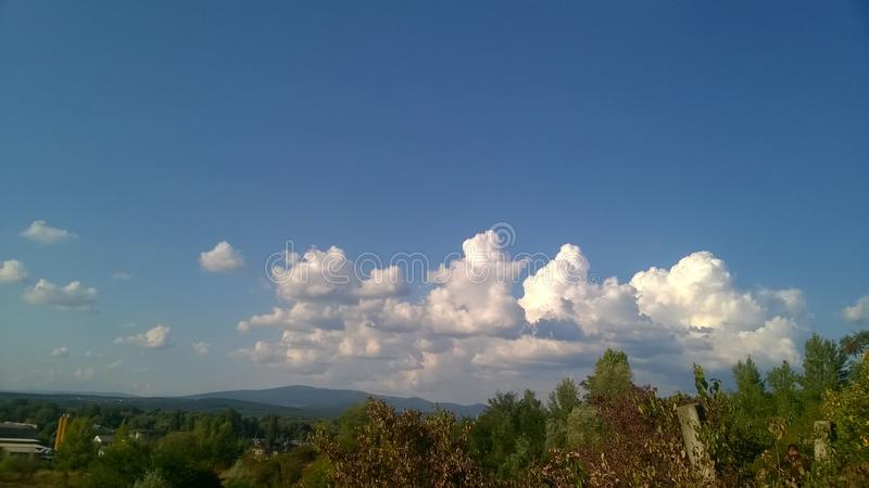 Nubes de cúmulo blancas sobre las montañas verdes imágenes de archivo libres de regalías