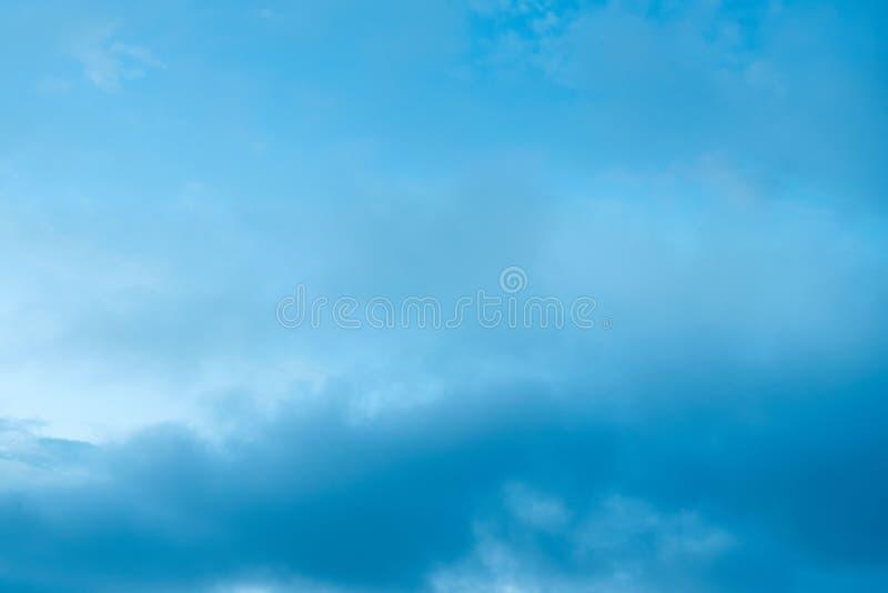Nubes de cúmulo de la puesta del sol con el fondo borroso del cielo azul de la puesta del sol defocusing imagenes de archivo
