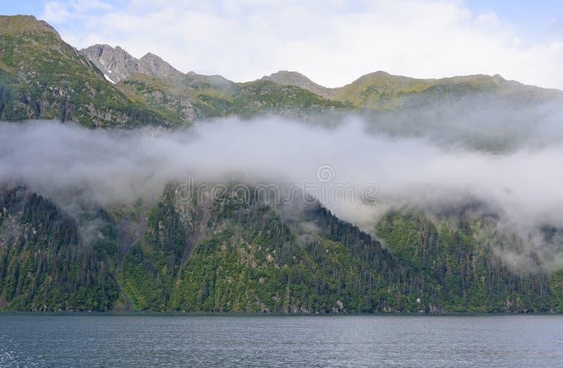 Nubes de la mañana en un fiordo del océano imagenes de archivo