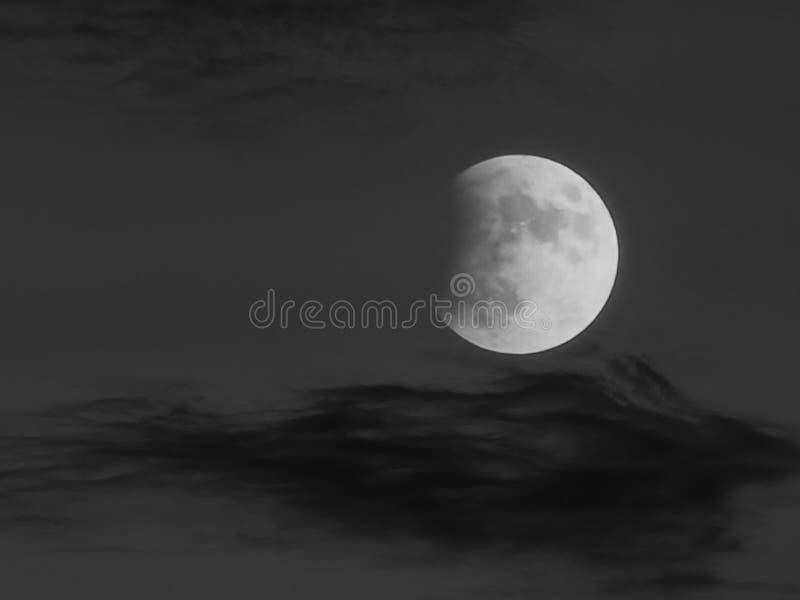 Nubes de la pizca del eclipse lunar sobre hora azul foto de archivo
