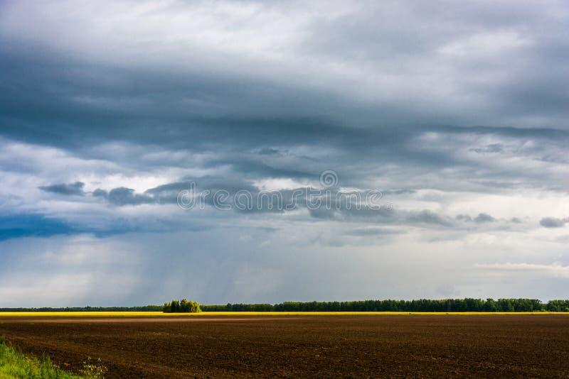 Nubes de lluvia y campo arado foto de archivo