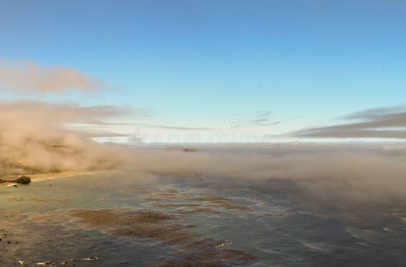 Nubes de mentira bajas sobre humedales costeros en la salida del sol foto de archivo